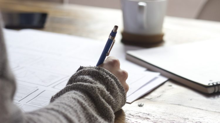A person writing on a piece of paper with a coffee cup in front of them