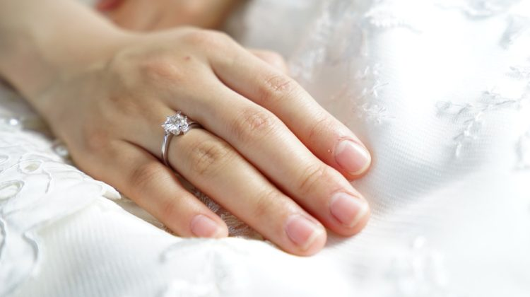 A woman's hand on a pillow displaying her engagement ring