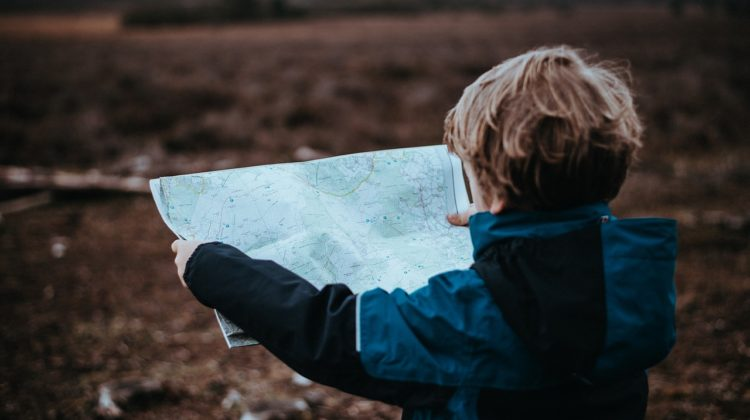 Child holding out a map and looking at it